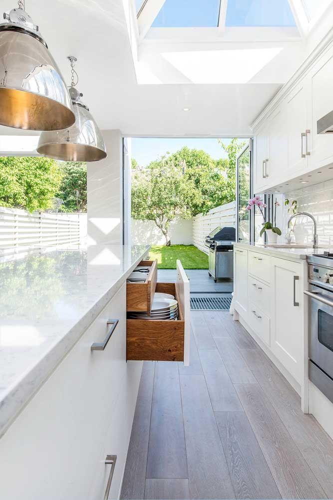 Cozinha corredor aberta para o quintal valorizando o contato entre a área externa e interna da casa