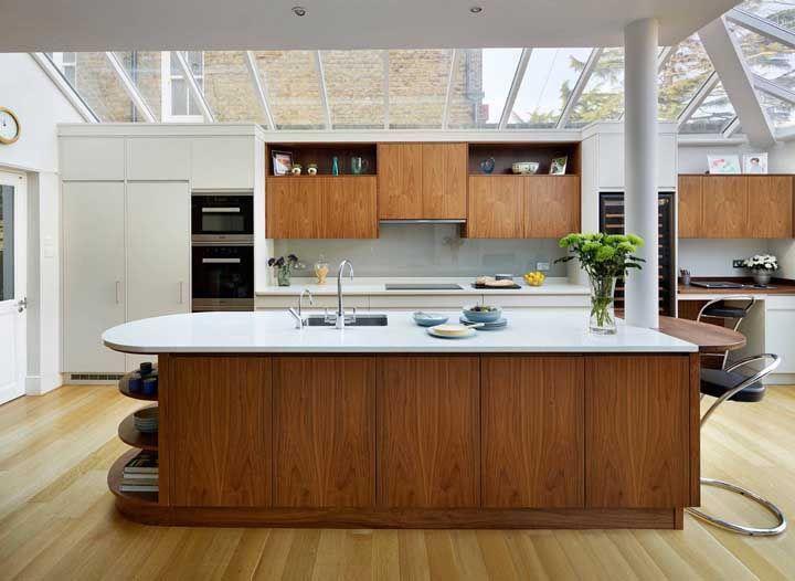 A ilha com detalhes em madeira acomoda tranquilamente os convidados da casa; o teto de vidro é um luxo à parte
