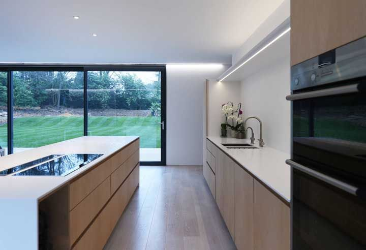 A integração com a área externa fica mais completa com a porta de vidro, perceba que mesmo estando fechada a paisagem se insere no ambiente