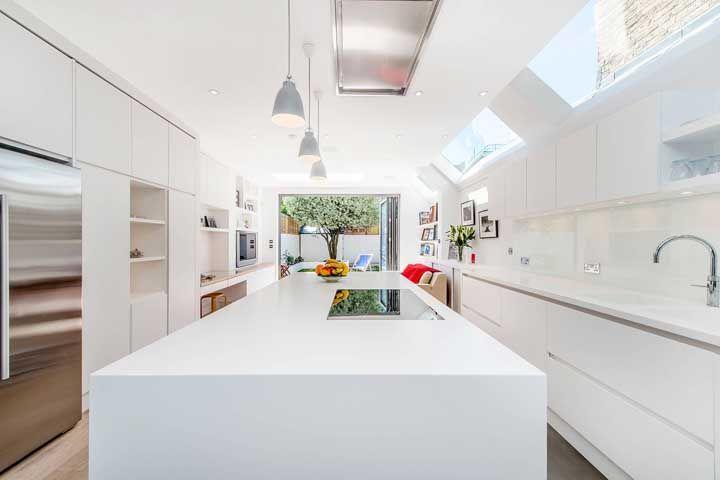 Espaço não é problema nessa cozinha aberta para o quintal, apesar do formato retangular