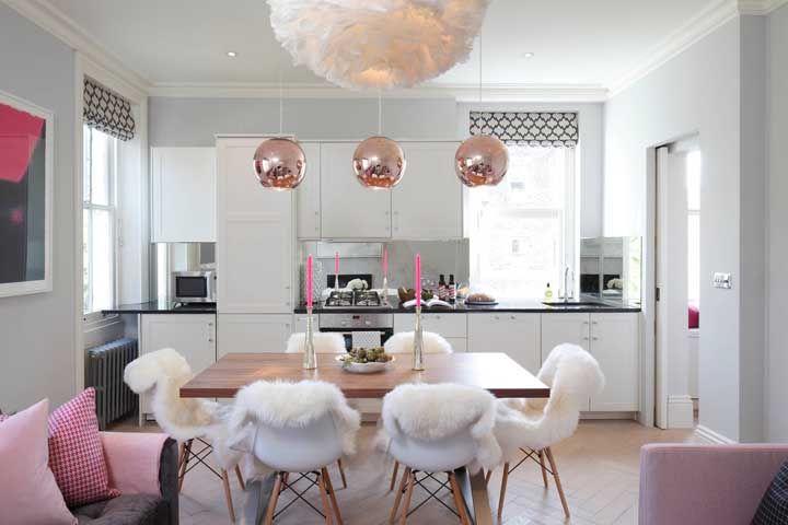 Ocupando apenas uma das paredes, a cozinha se tornou o pano de fundo da sala de jantar e da sala de estar
