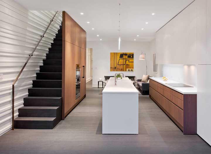 Cozinha aberta branca com detalhes em madeira; repare que o espaço sob a escada foi aproveitado para a instalação do forno