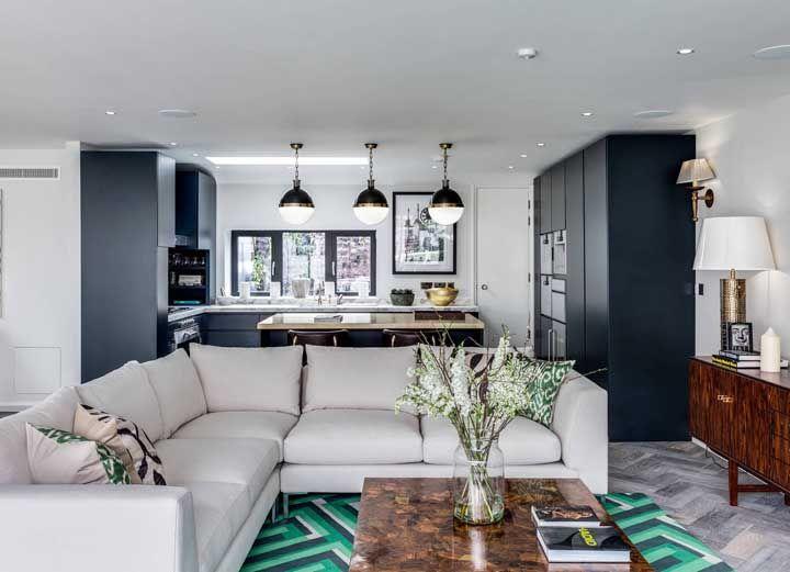 O azul da cozinha aberta segue na sala de estar, mas de modo mais sutil, apenas no tapete combinado ao verde