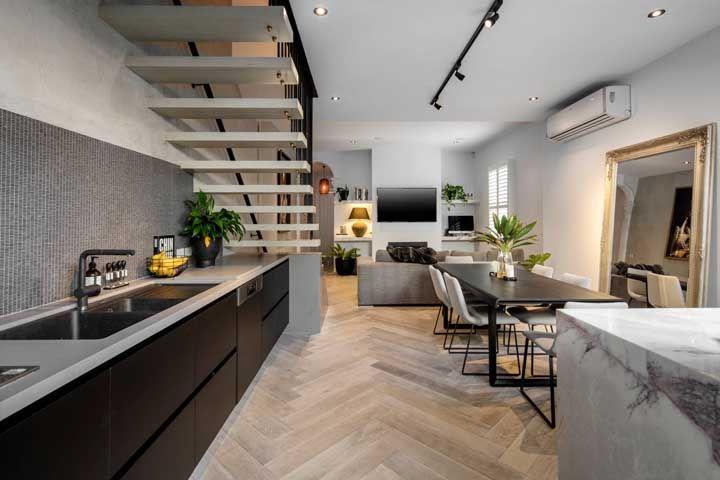 E como espaço é algo valioso dentro das casas atuais, nada mais justo do que aproveitar o vão embaixo da escada; aqui, por exemplo, ele acomoda a cozinha aberta
