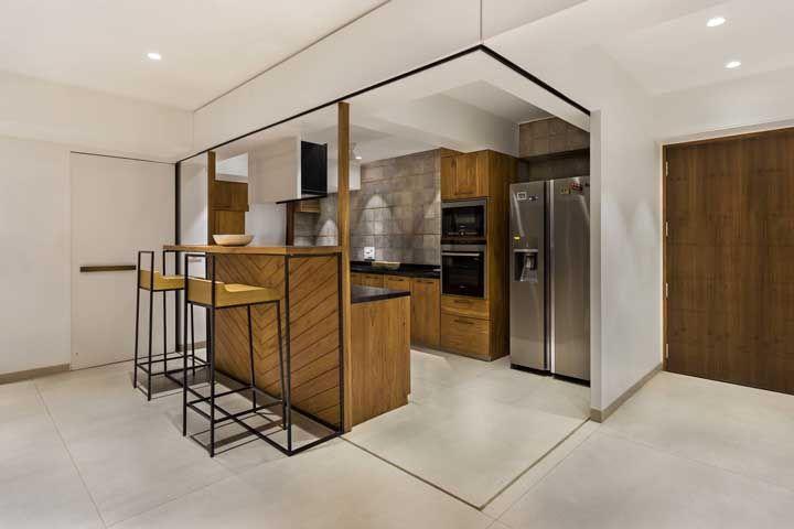 Cozinha aberta? Só quando o morador quiser, repare que ela possui portas de madeira que correm sobre o trilho facilitando o abrir e fechar