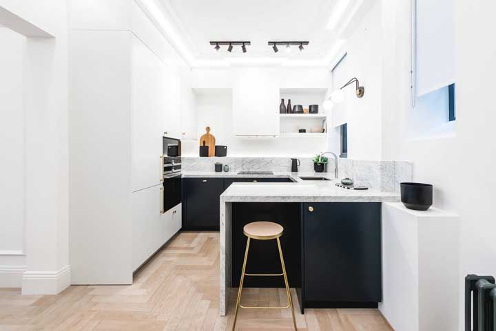 Cozinha aberta branca com detalhes em dourado e um toque de azul para quebrar a monotonia