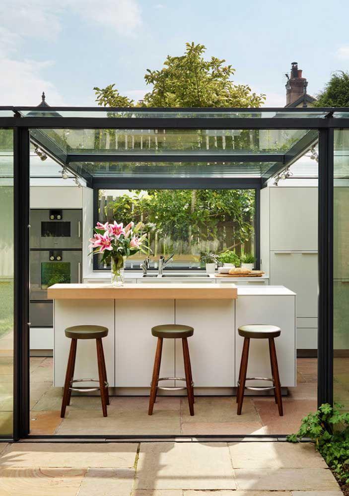 O pergolado com cobertura de vidro deixa a cozinha aberta para o quintal mais despojada e descontraída