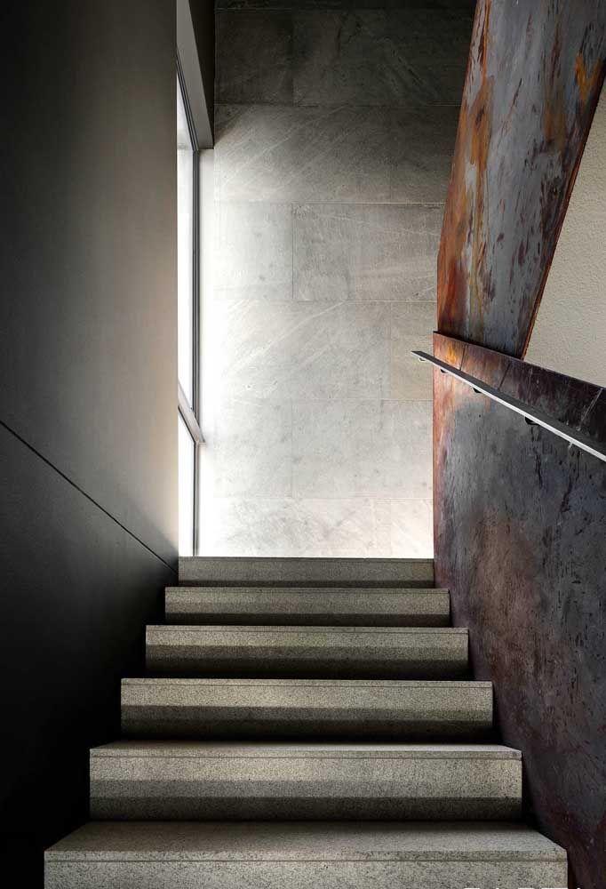 O granito de tom claro reveste toda essa escada emoldura pela parede aço corten