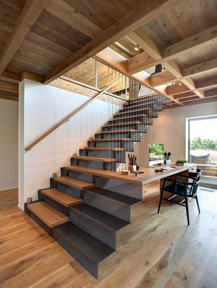 Criatividade é a alma do design de interiores: aqui, madeira e aço se combinam para formar a escada e a mesa do escritório