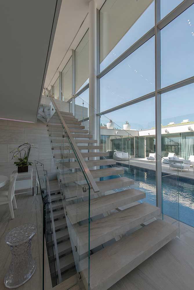 O mármore de tom neutro foi o escolhido para esse projeto clean e moderno; o guarda corpo de vidro traz ainda mais suavidade para a escada