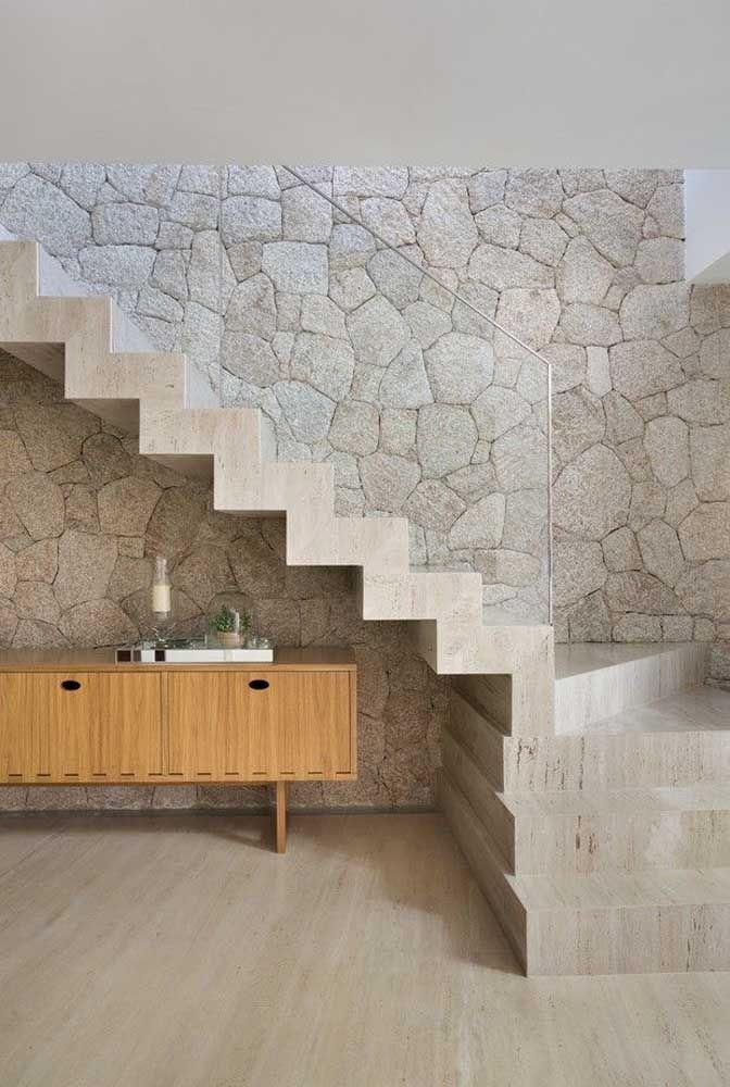 A sofisticação do mármore contrastada pela rusticidade das pedras brutas na parede
