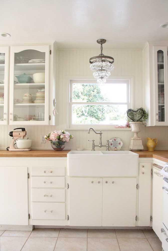 A cozinha branca entrou no estilo Shabby Chic com as flores delicadas sobre a bancada, a batedeira vintage e o vaso desgastado de cerâmica ao lado