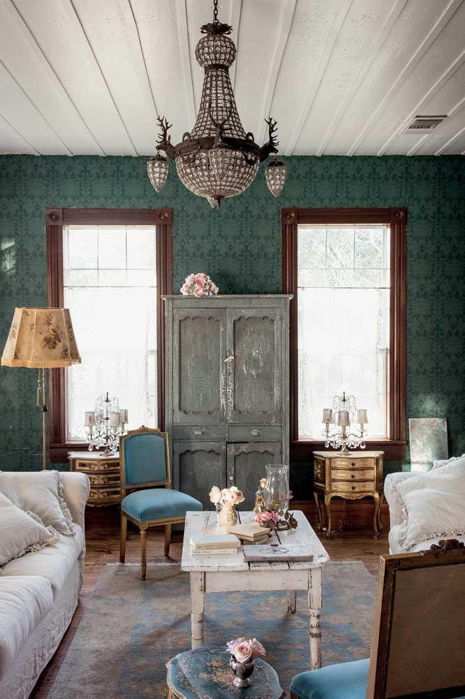 Uma típica decoração Shabby Chic é feita assim: sobriedade e elegância presentes no verde escuro da parede, no lustre e na madeira contrastados pelo aspecto envelhecido do armário e da mesa de centro