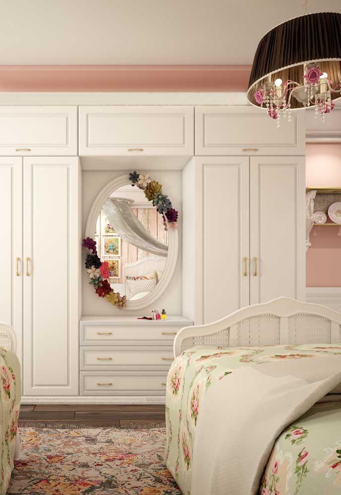 O Shabby Chic desse quarto é formado por flores: estampadas na roupa de cama, no tapete e na moldura do espelho