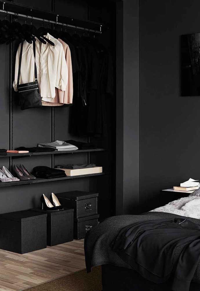 Moderno, esse closet aberto preto apostou no uso de araras e caixas para manter a organização