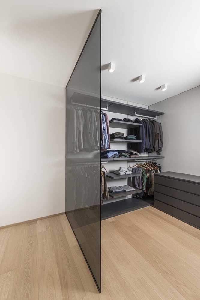 A parede de vidro divide suavemente o closet do restante do quarto