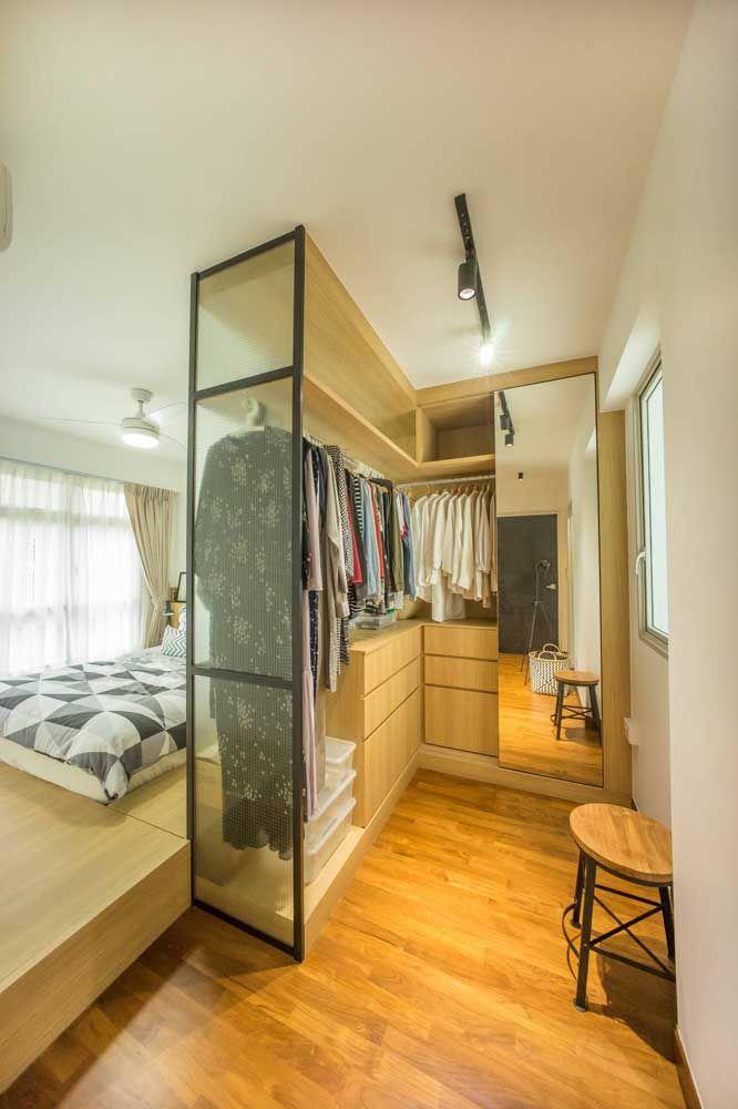 O banco e o espelho trazem conforto e praticidade para o closet aberto