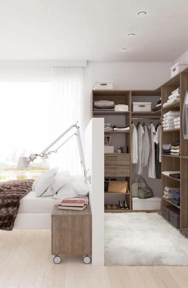 A parede que forma a cabeceira da cama também serve o closet aberto