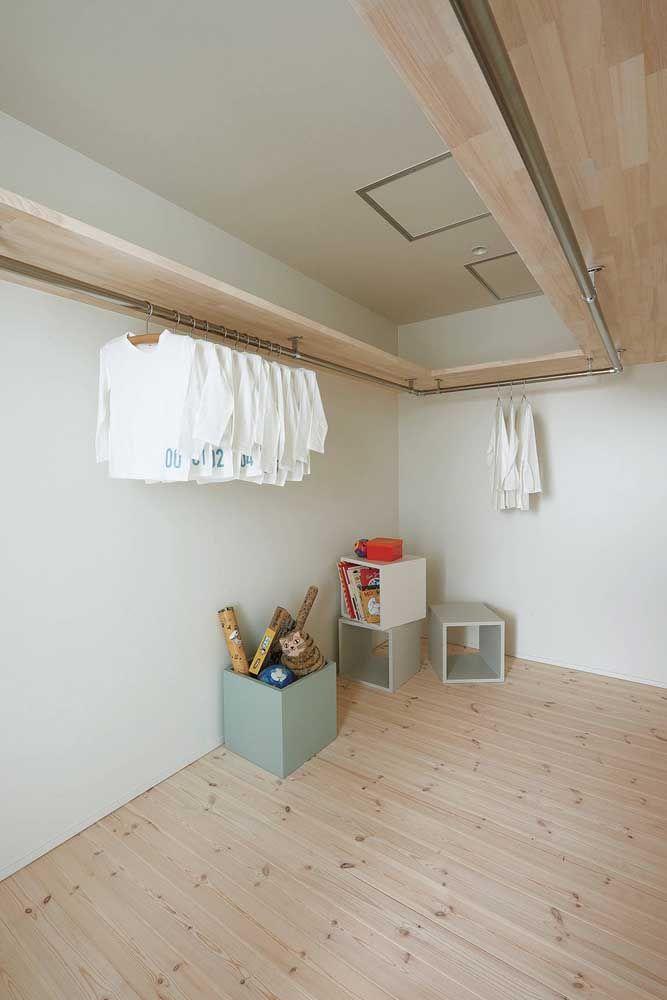A proposta nesse closet foi montar uma peça única de madeira que contorna as paredes do quarto e funciona como prateleira e arara