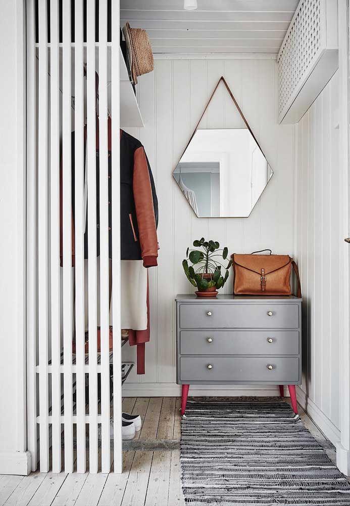 As ripas de madeira dão um pequeno toque de privacidade ao closet aberto, a cômoda de estilo retrô e o espelho moderno fecham a proposta de organização e decoração