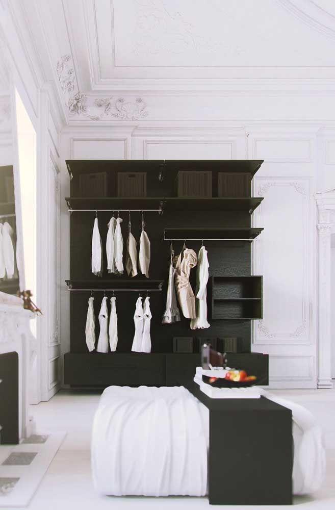 O quarto de estilo clássico ganhou um closet aberto feito com caixas, prateleiras, araras e nichos