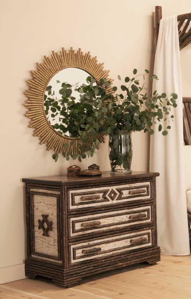 A cômoda rústica, cheia de entalhes, ganhou o acompanhamento de um vaso verde e um belo espelho de moldura dourada