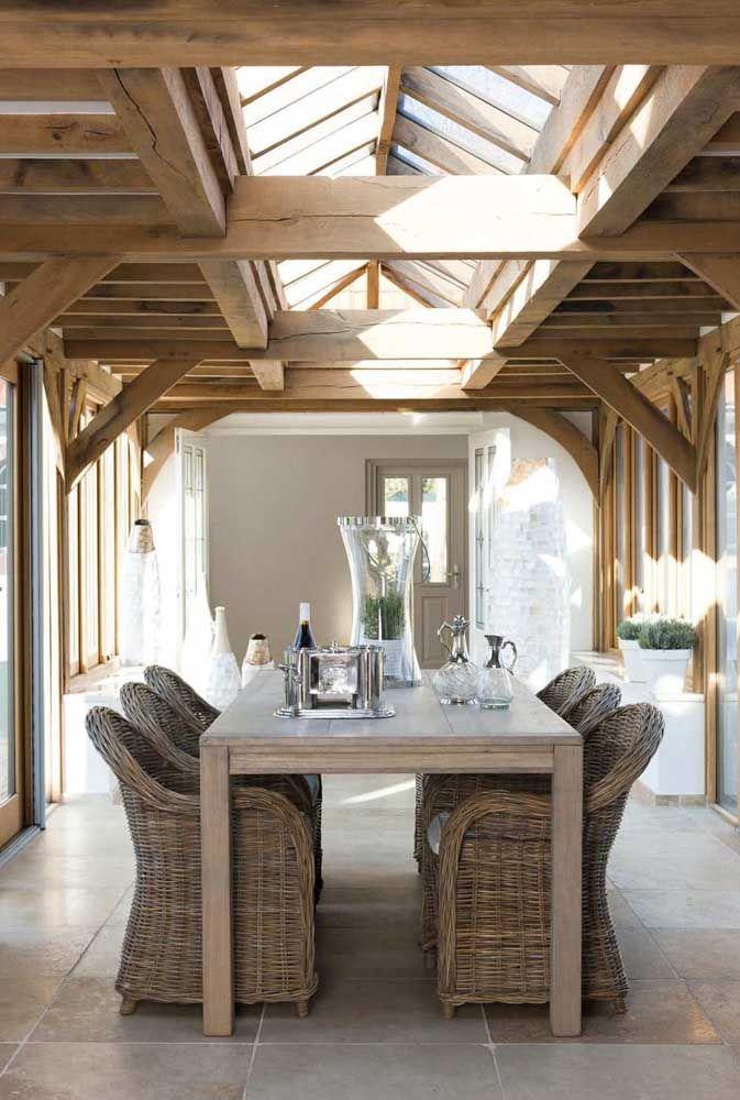 O visual do telhado de madeira aparente se completa com a mesa e as poltronas rústicas