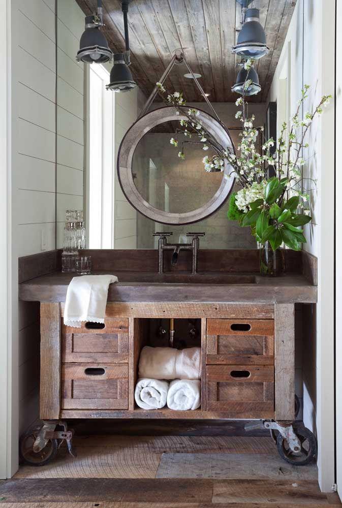 O banheiro da casa também merece toda a atenção na hora de decorar; esse aqui, por exemplo, ganhou uma bancada de madeira rústica com direito até a rodinhas de ferro