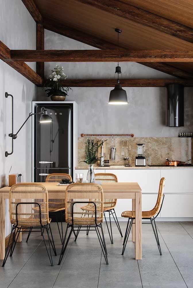 Integração entre estilos e materiais: nessa sala de jantar a madeira da mesa de jantar se alinha com as cadeiras de design moderno feitas em fibra natural e ferro