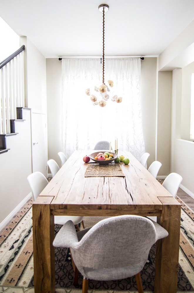 Um belo tapete e cadeiras modernas para acompanhar a mesa rústica de madeira