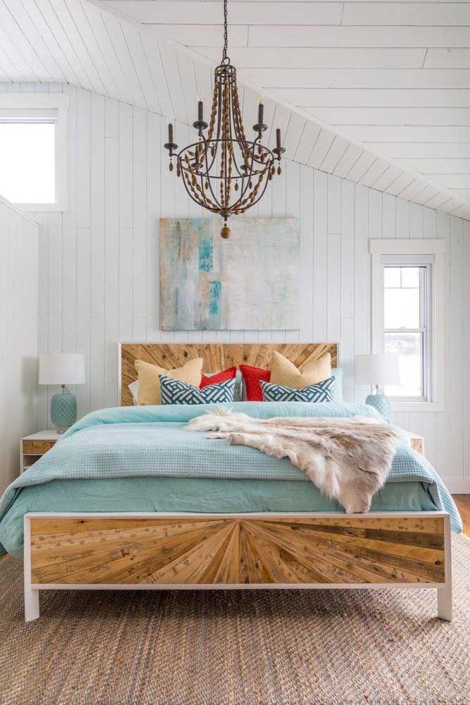Contraste a rusticidade da cama com um lustre pendente e clássico de cristal
