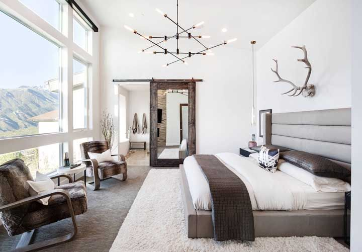 O quarto de móveis rústicos fica ainda mais bonito com a paisagem natural que invade o quarto pela janela