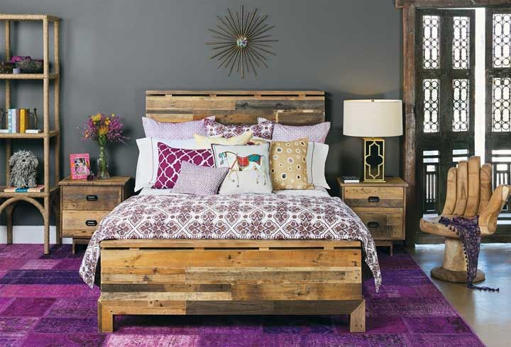 Os tons de roxo do tapete emolduram a cama rústica de madeira, uma combinação marcante e cheia de personalidade