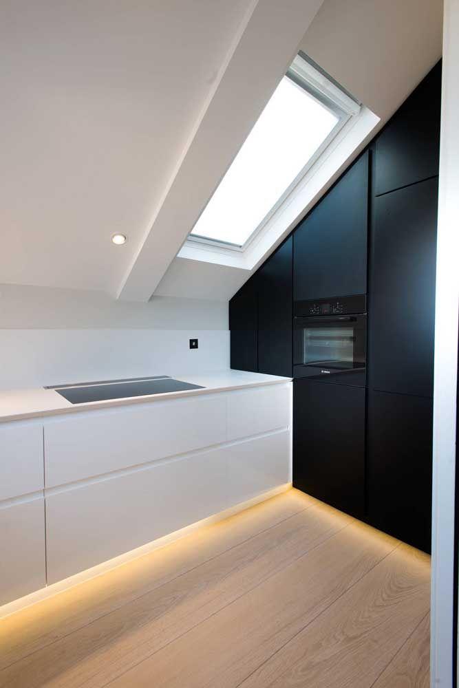 Cozinha preta e branca feita em Corian; a iluminação integrada dá o toque final de estilo e elegância ao projeto