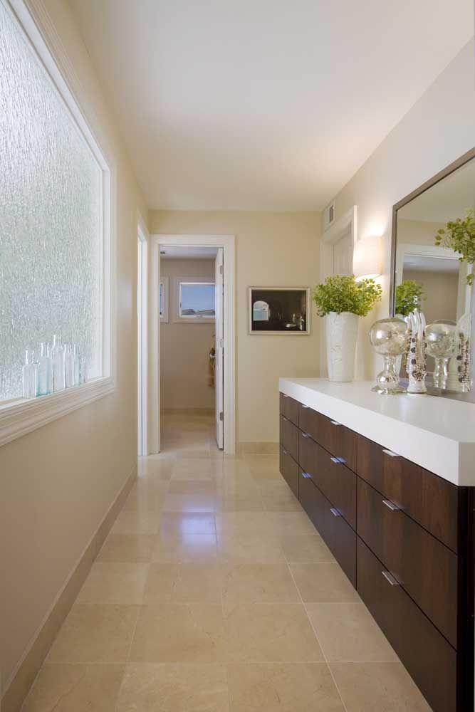 A bancada branca de Corian ressalta a beleza natural do armário de madeira escura.