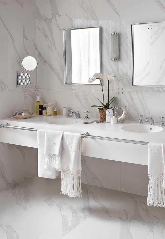 Um banheiro de luxo se faz assim: mármore para revestir parede e chão e Corian para a bancada