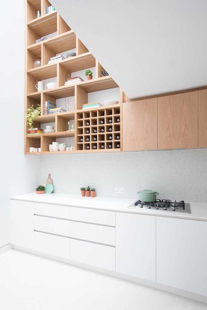 Bancada de Corian branco e armário na mesma cor; para gerar um pouco de contraste, a parte de cima da cozinha foi planejada em tom de madeira