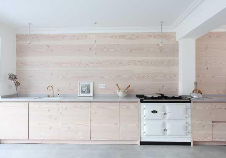 Bancada de Corian cinza combinada a madeira de tom claro dos armários e da parede