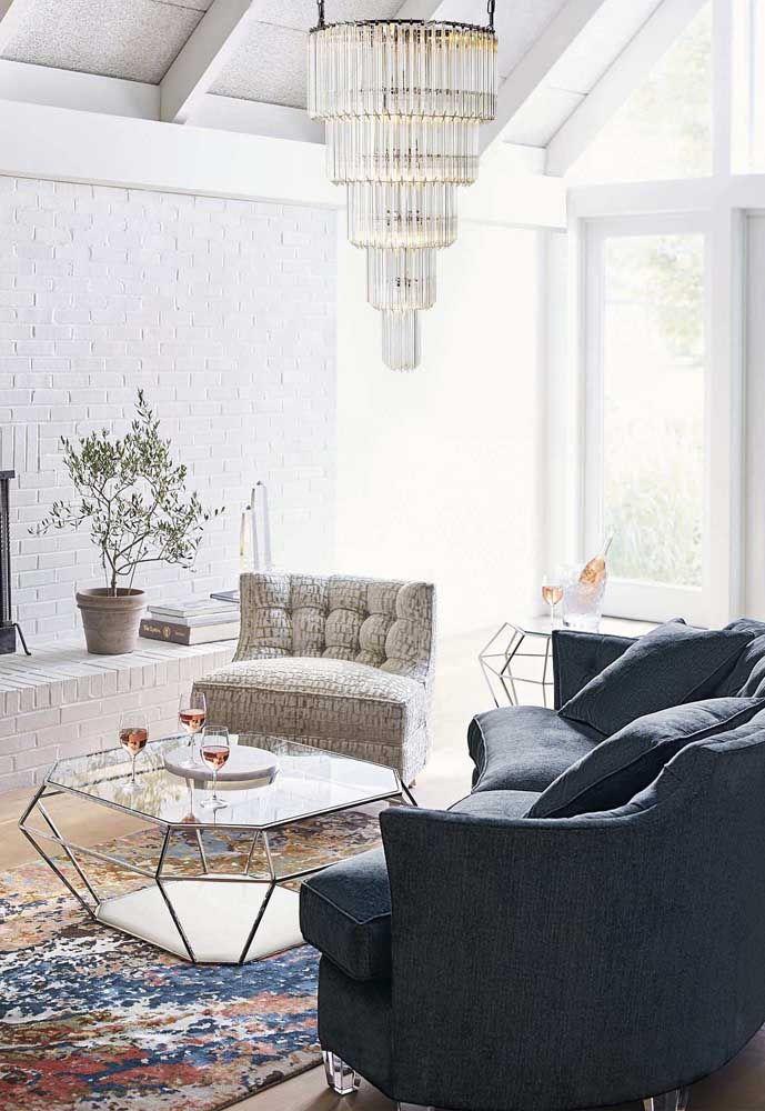 O moderno e o clássico se unem nessa sala de estar, a começar pelo lustre de cristal