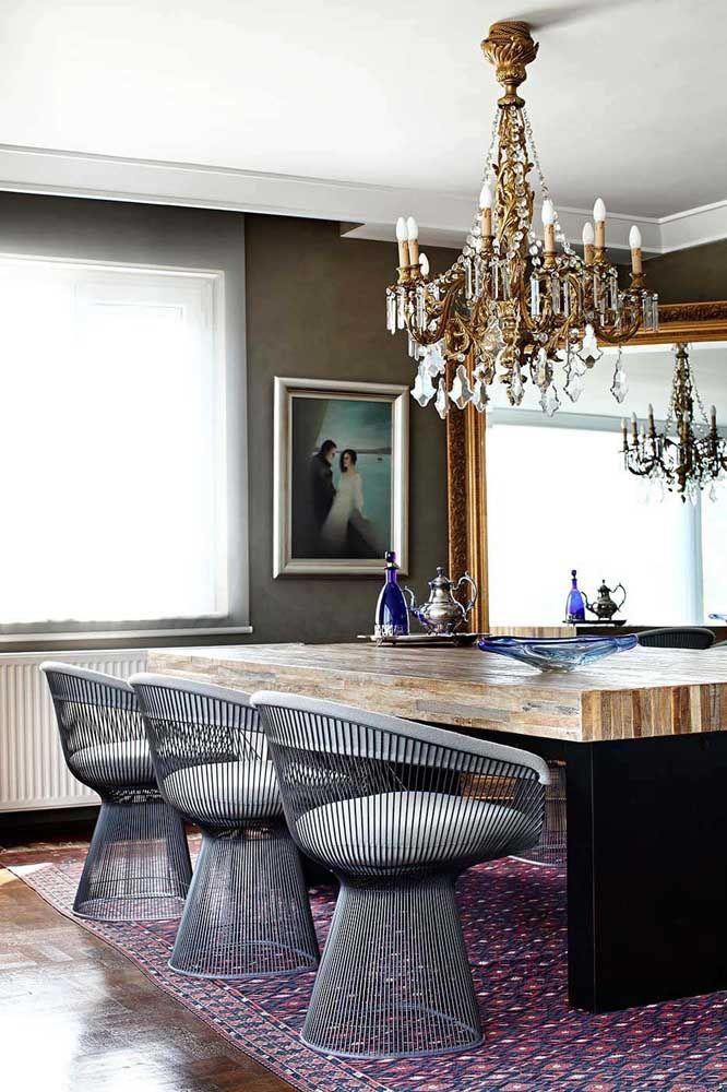 O metal envelhecido do lustre candelabro evoca uma atmosfera clássica e vintage para essa sala de jantar que mescla o moderno e o rústico