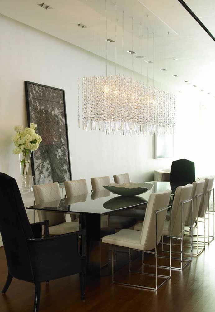 O lustre retangular acompanha o formato da mesa de jantar e traz uma iluminação especial para o ambiente