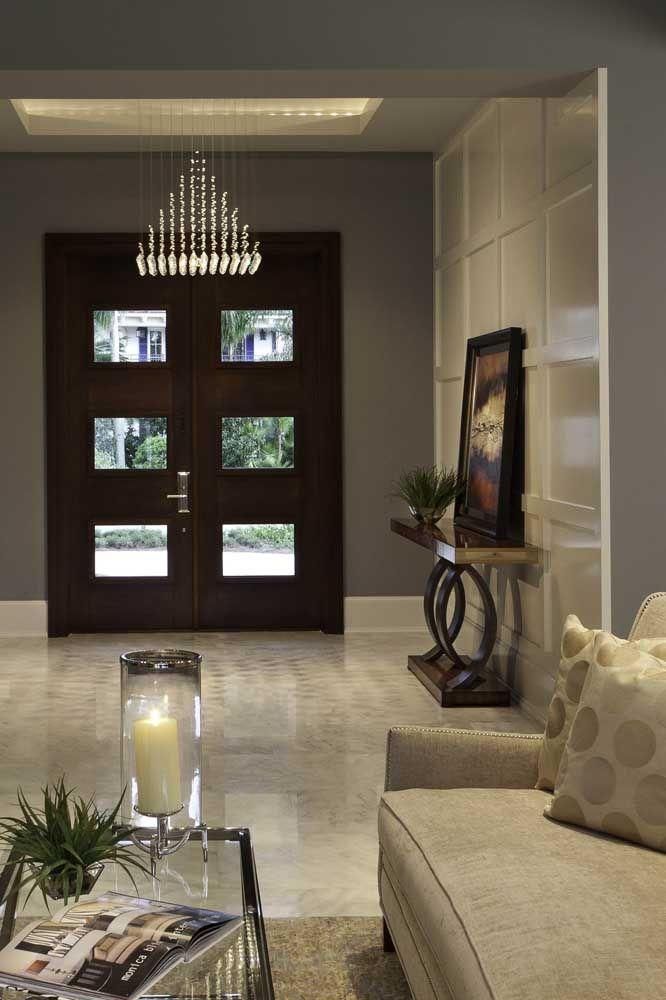 O lustre de formato triangular dá as boas vindas a quem chega no hall de entrada