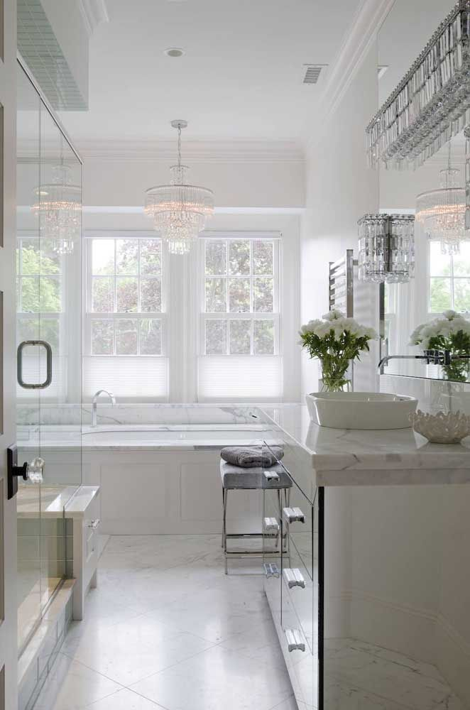 Lustre de cristal valoriza a decor branca e clean do banheiro