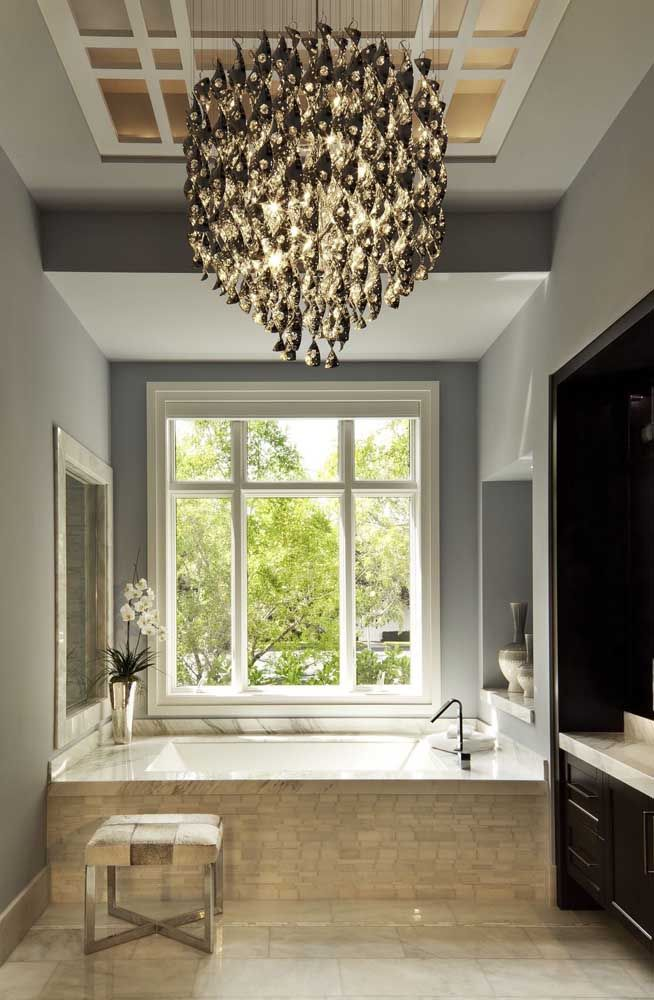A decor simples e sóbria desse banheiro se transformou com o enorme lustre preto de cristal
