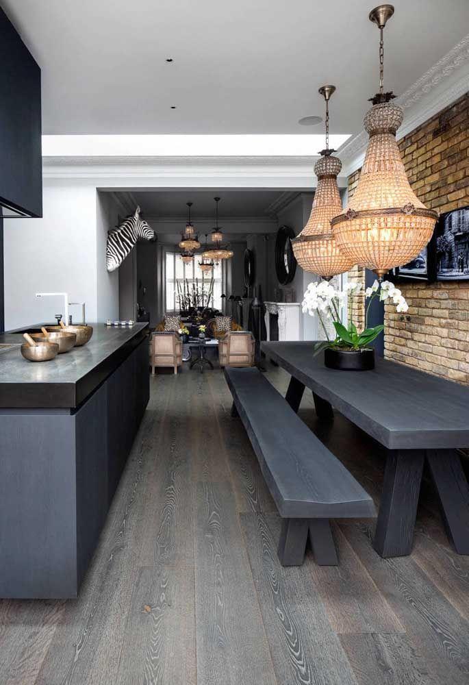 Um mix de texturas e estilos nessa sala de jantar, passando, sobretudo, pela parede de tijolinhos e os dois lustres de cristal