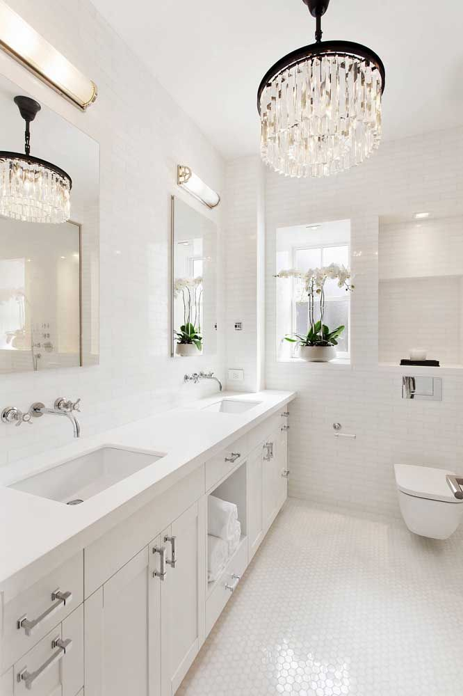 Para o banheiro branco e minimalista, um lustre de cristal com detalhe preto