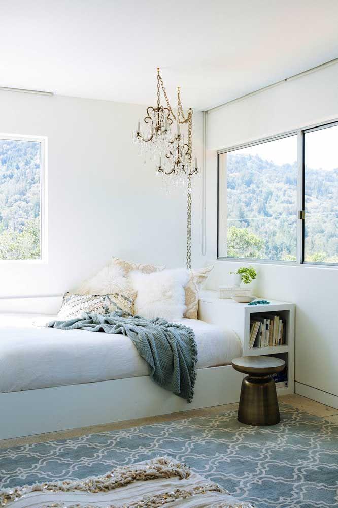 Sobre a cama, o lustre de cristal traz uma iluminação direcionada com muito requinte e glamour