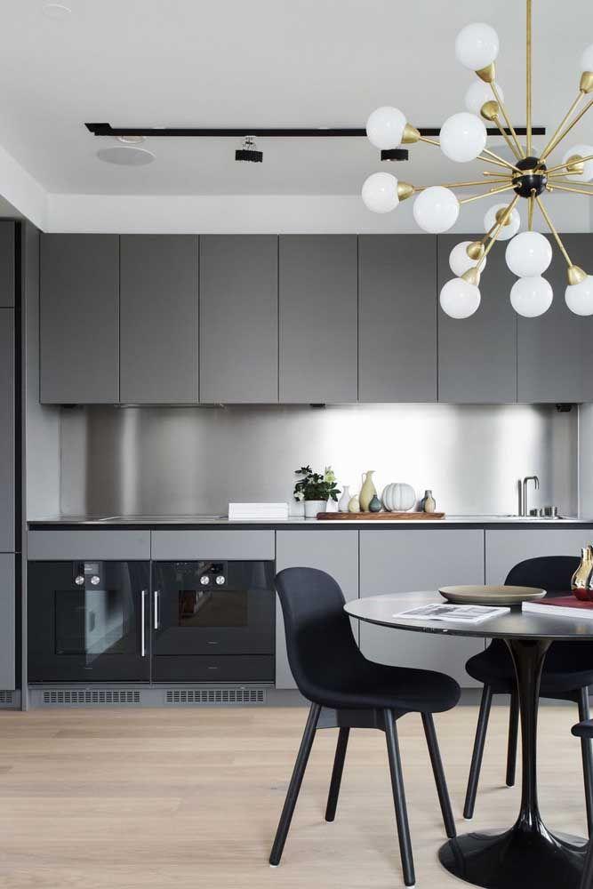 O lustre moderno com diversas ramificações foi colocado sobre a mesa de jantar da cozinha integrada