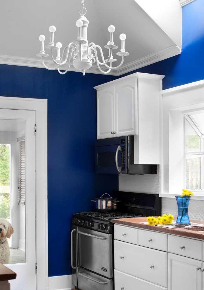O lustre branco simples estilo candelabro se destaca frente à parede azul