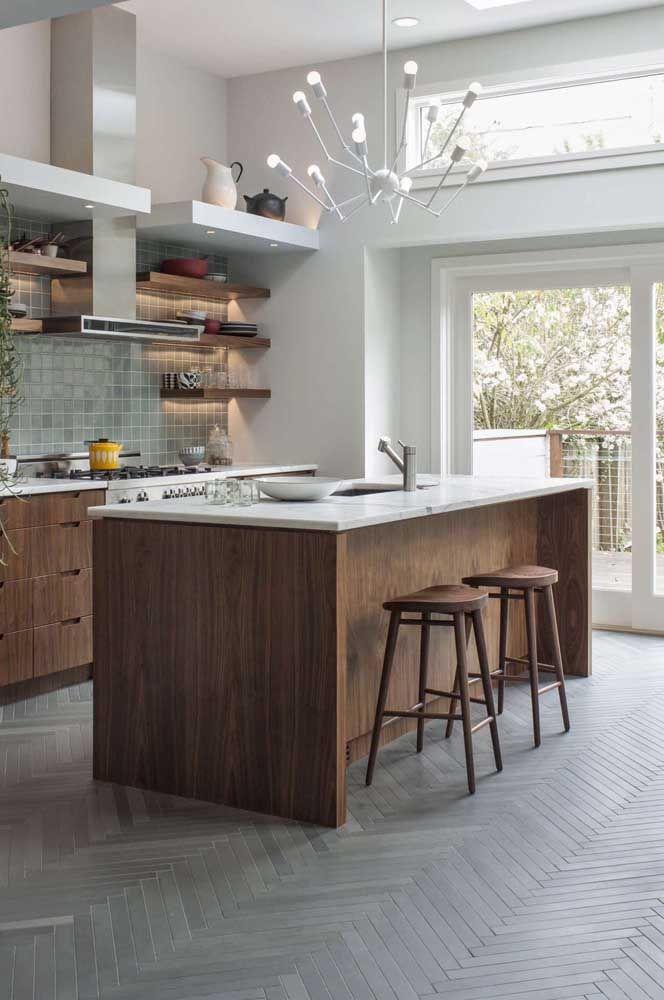 Aqui nessa cozinha, o lustre sobre a bancada cumpre o papel de fonte principal de iluminação